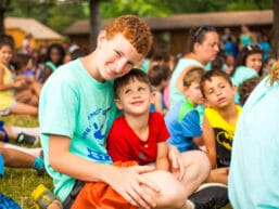 Two campers smiling at an assembly.