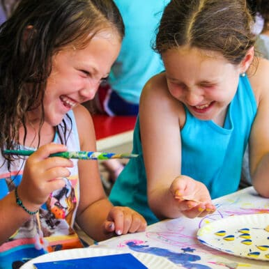 Two girls sitting at a table painting and laughing.