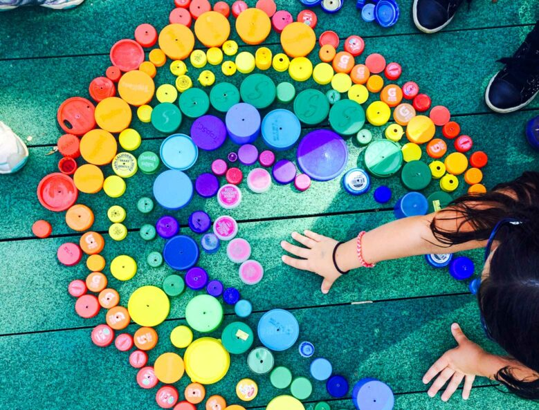Campers creating a rainbow mosaic with bottle caps.
