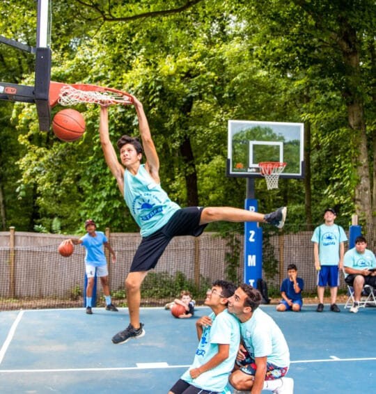 A camper dunking a basketball while his friends watch.