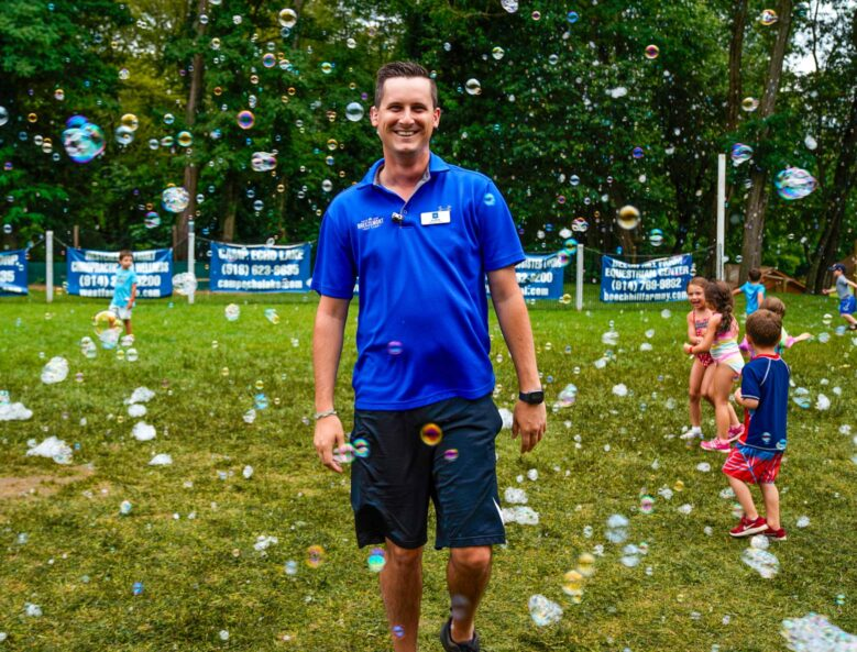 A camp staff member smiling while soap bubbles are floating in the air.
