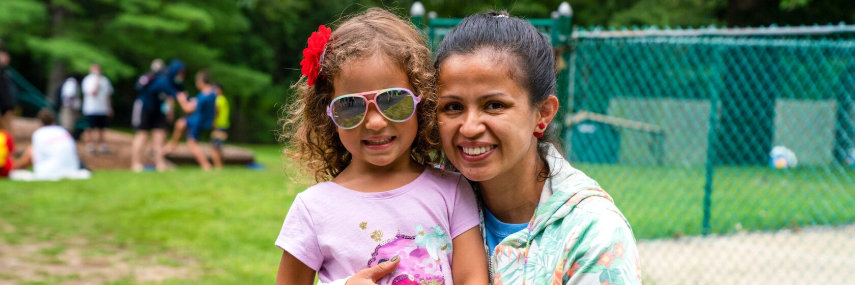 A mother and daughter smiling at camp.
