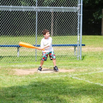 A camper standing at homebase ready to bat during a game of baseball.