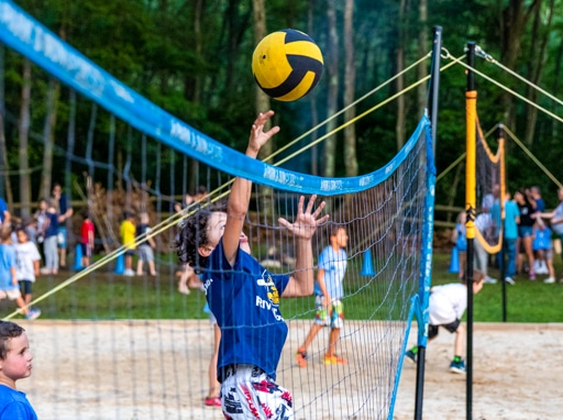 Campers playing volleyball on the sand courts.