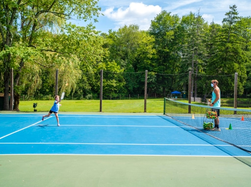 A camper learning how to play tennis on the courts.