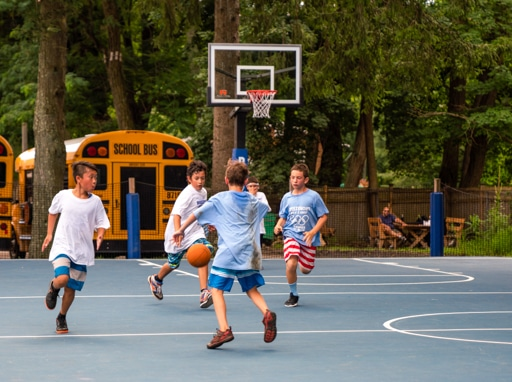 Campers playing basketball on the basketball courts on campus.