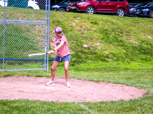 Campers playing softball on the baseball fields on campus.