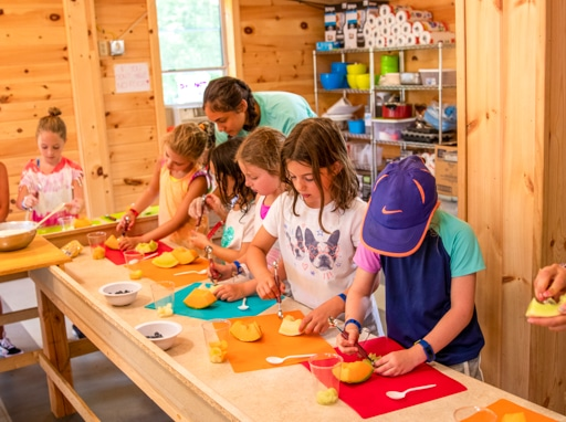 Campers preparing fruit in the kitchen.