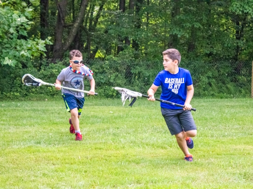 Campers running on the lacrosse field.