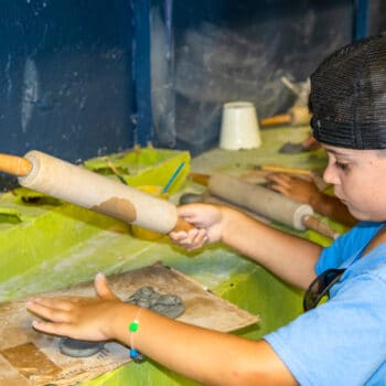 A camper shaping an object during pottery activities.