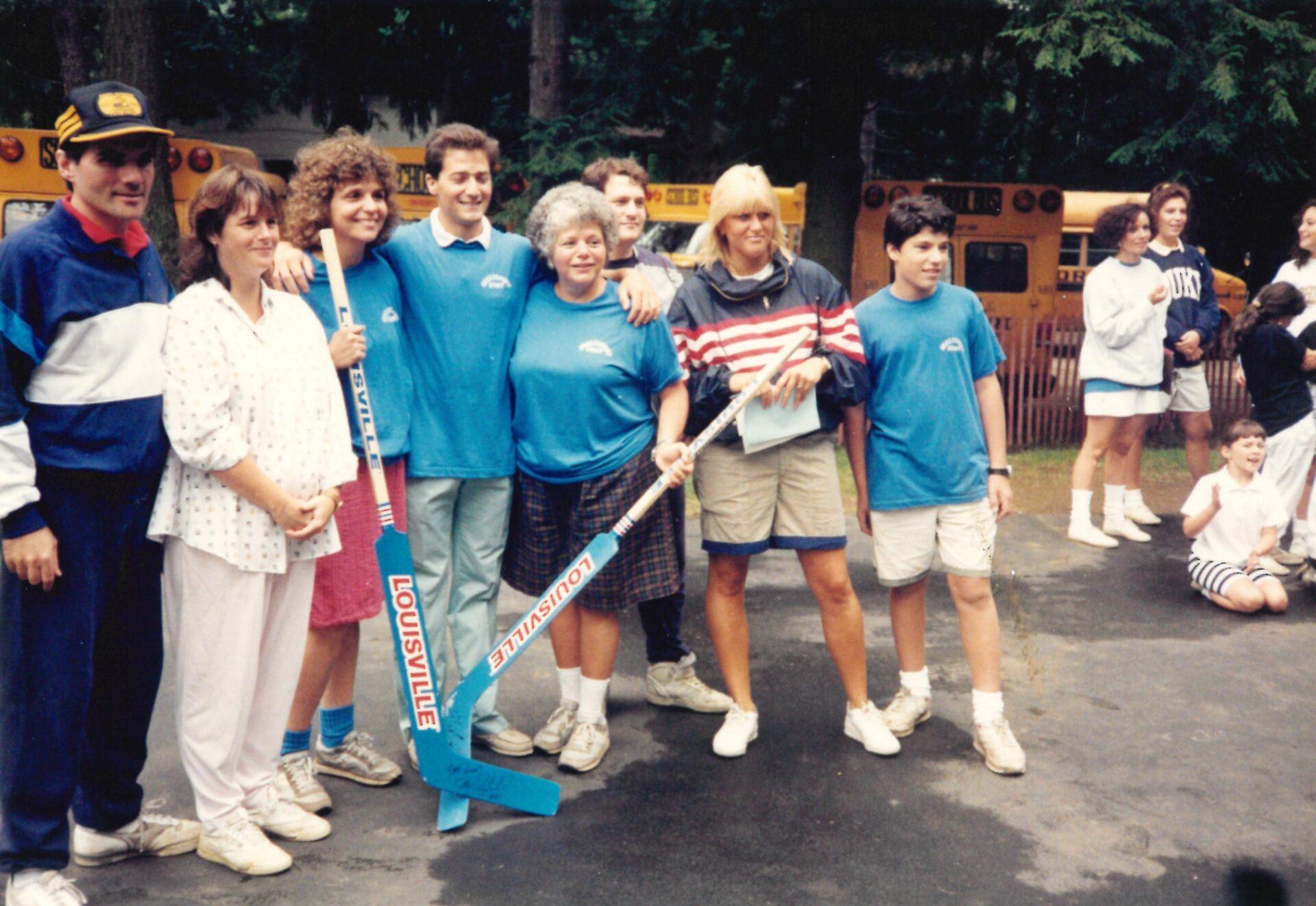 Camp staff posing with hockey sticks.