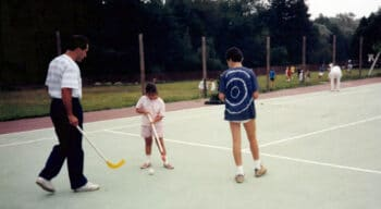 Campers playing hockey on a court.