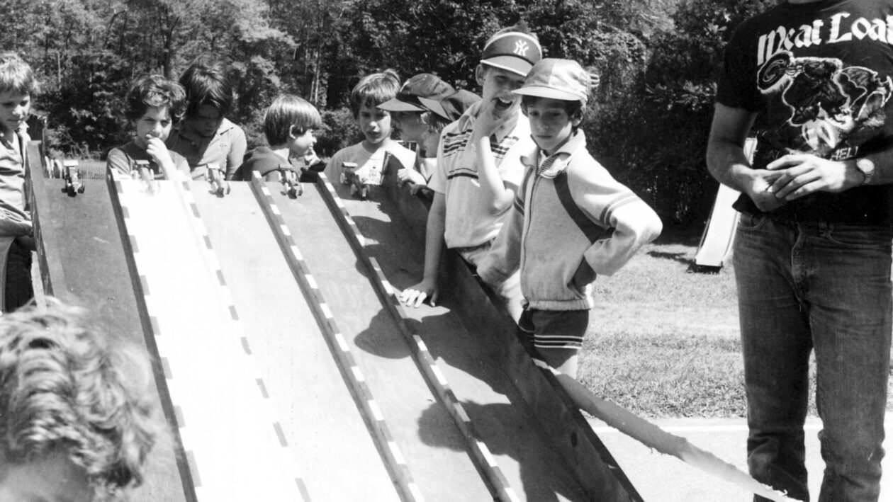 Campers racing miniature cars down a track.