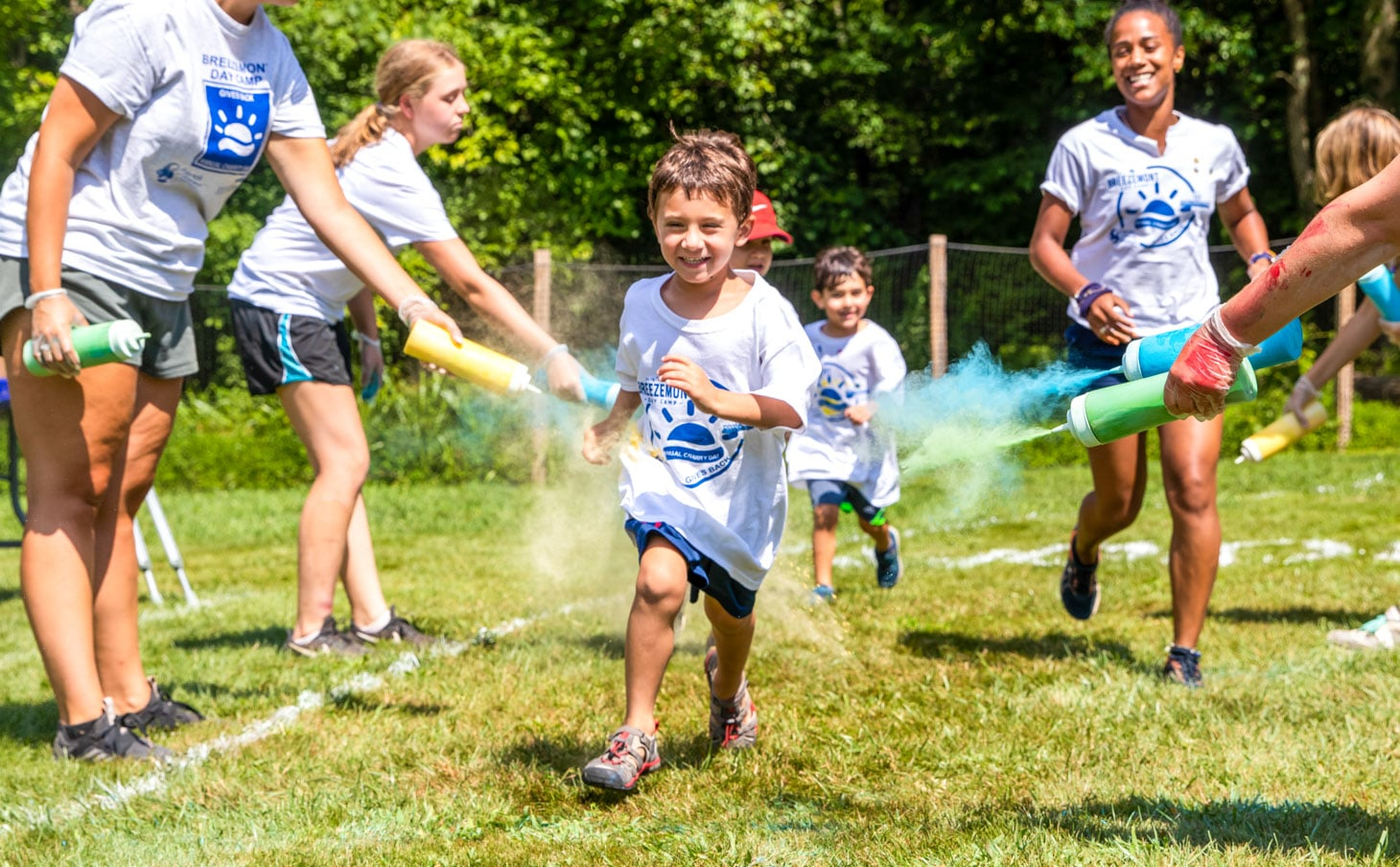 A camper running through colorful dust while smiling and laughing.